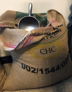 Burlap sack of green coffee beans with a steel scooper.