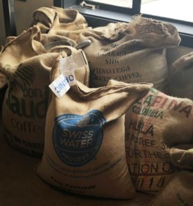 Six large burlap sacks of raw coffee beans.
