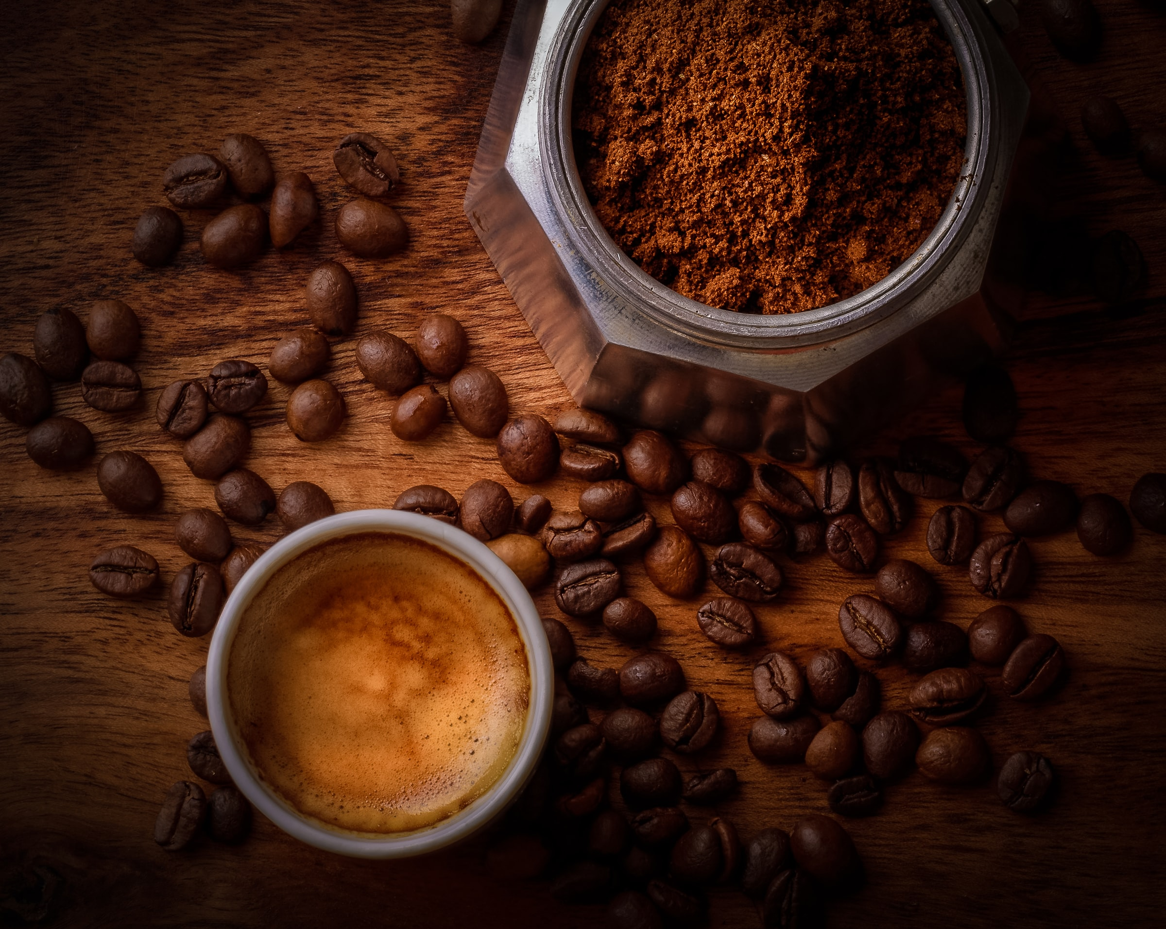 Cup of espresso next to an espresso pot filled with ground coffee, surrounded by whole roasted coffee beans.