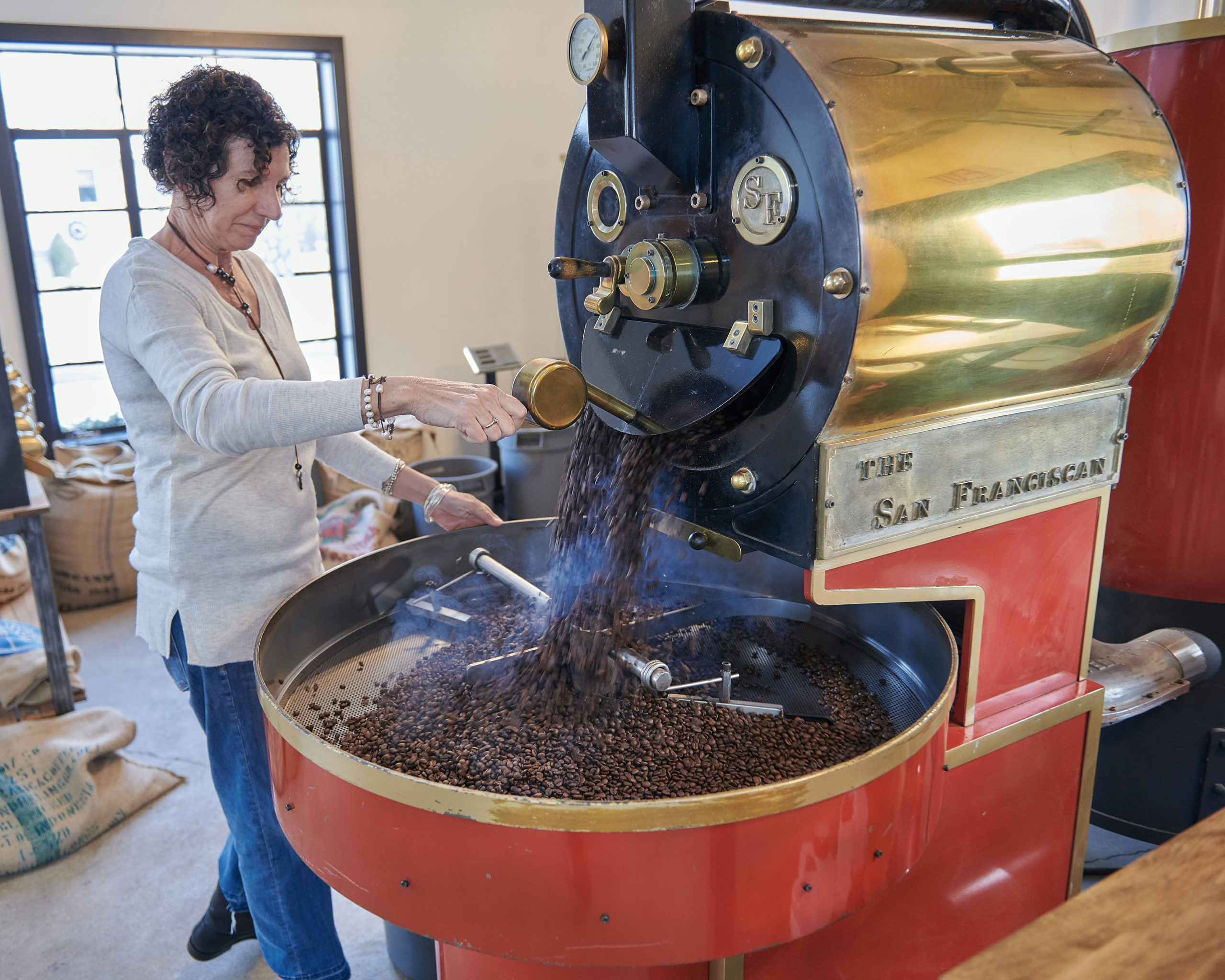 Kate stirring roasted coffee beans in the roaster.