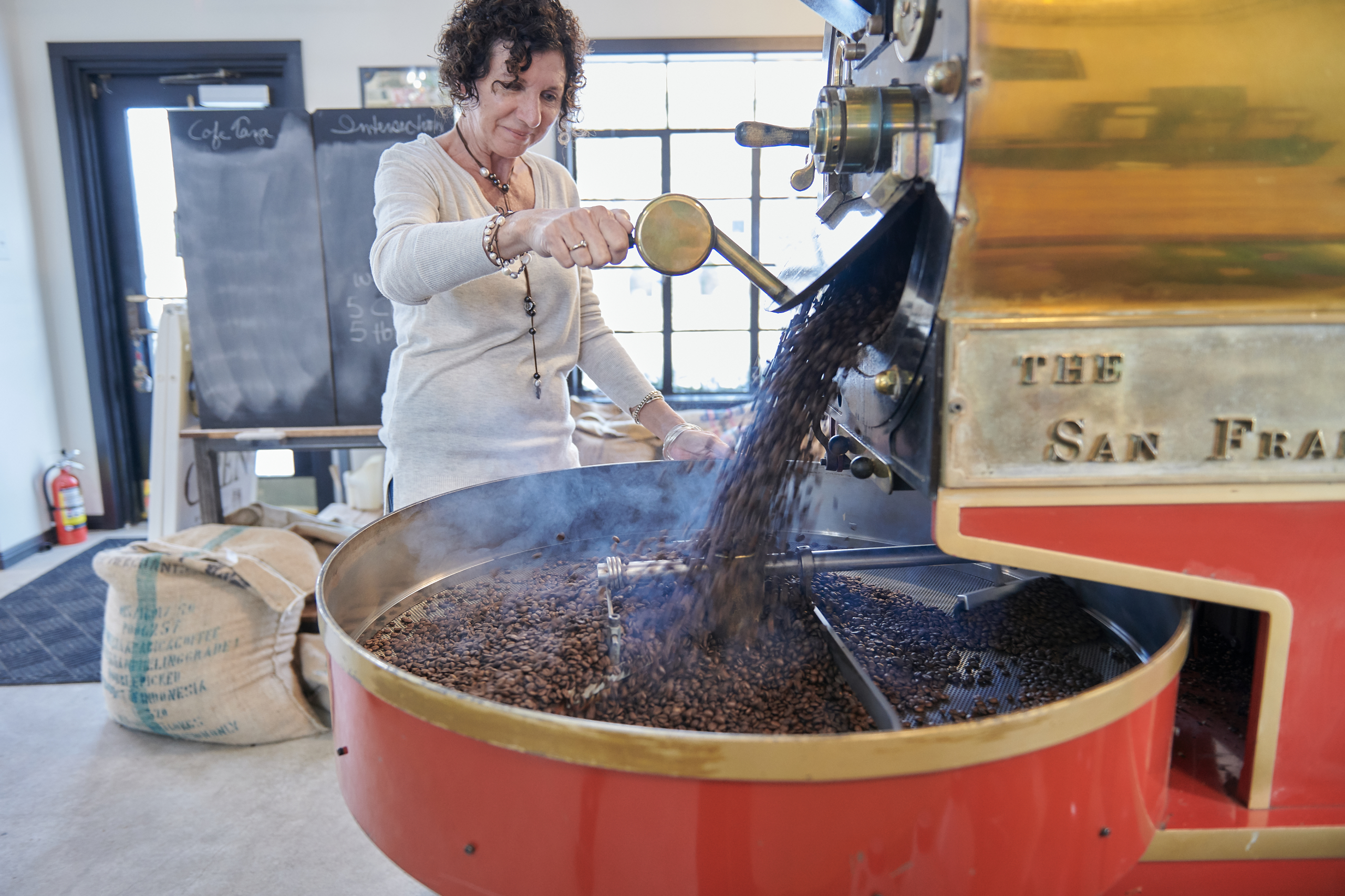Kate pouring roasted beans from the roaster.